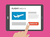 Hand touching screen of tablet computer with check in button and airplane icon on screen. Concept of flight check in mobile application