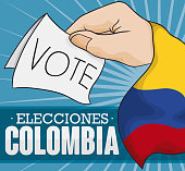 Hand with Colombian flag holding a vote for electoral contest in Colombia (texts written in Spanish).