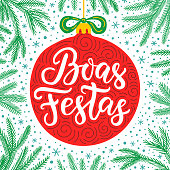 Hand-drawn lettering inscription Happy holidays in Portuguese language inside the cartoon style red ball with bow and fir tree branches on the snowflake background. EPS 10 vector illustration