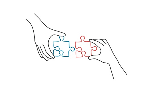 Hands connecting jigsaw puzzle.