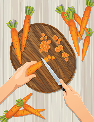 Hands From Above Cutting Carrots On A Wood Cutting Board