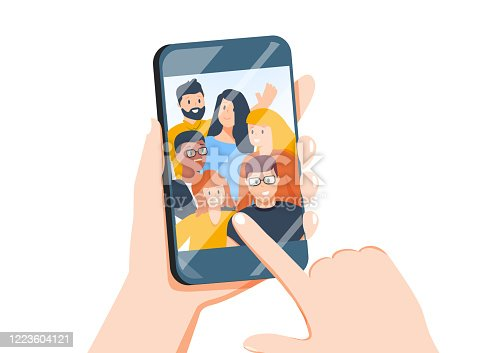 istock Hands holding mobile phone with happy boys and girls displaying on screen. Friends posing for selfie, group of people 1223604121