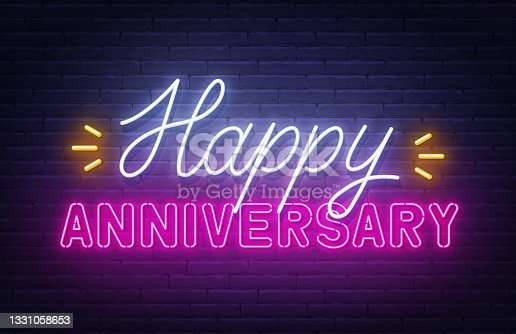 istock Happy anniversary neon text. Greeting card on brick wall background. 1331058653