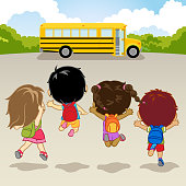 Four kids are happily running and jumping towards the school bus