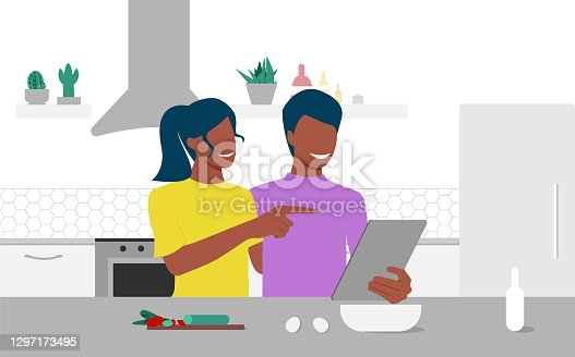 istock Happy black couple looks on tablet and choose recipe in their kitchen. Online culinary school. Online courses, e-learning. Eps 10. 1297173495