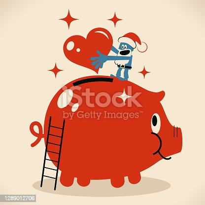 istock Happy blue Santa Claus putting a heart symbol into a large piggy bank 1289012706