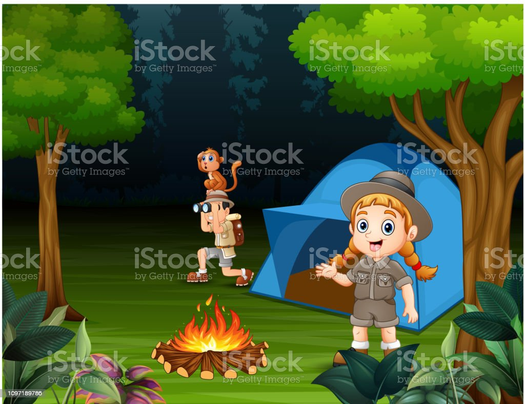 Happy children camping out in a forest
