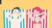 Happy couple sunbathing on the beach