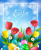Easter greeting card with realistic glossy 3D eggs, red and yellow flowers tulip and daisy. Handwriting inscription Happy Easter. Blue sky background. Template for cards, banners, posters, calendars, invitations.