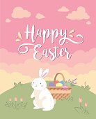 Happy Easter greeting card with the white rabbit and the basket of eggs on the lawn on the background pink sky and yellow clouds.