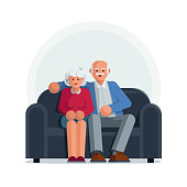 Happy elderly couple sitting on a sofa together
