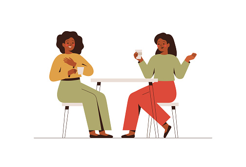 Happy female friends rest in the cafe and talk about something. Two black women spending time together at coffee break.