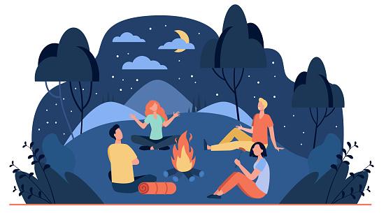 Happy friends sitting near campfire at summer night