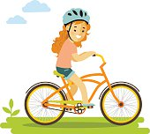 Smiling little girl in helmet riding on bicycle