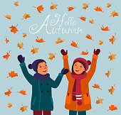 Happy kids having fun and playing with autumn leaves in park. Autumn landscape background
