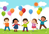 Happy kids jumping together and holding balloons