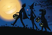 Vector illustration of three Trick or Treaters in silhouette going on their Halloween night quest for candy. First up is a boy dressed in a superhero costume with a bat style mask and cape. Next up is a little girl dressed as a witch with a glowing wand. Last, is a child dressed in a T-Rex dinosaur costume. Overhead, the golden full moon gleefully watches the event as leaves scatter in the night blue background..