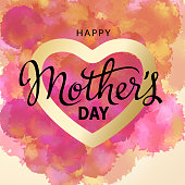 Celebrating the Mother's Day with gold colored heart shape and calligraphy on the pink watercolor background