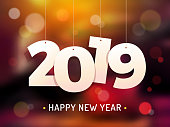 Happy 2019 New Year's Eve Celebration concept with numbers hanging on threads with bokeh blurred background behind vector illustration