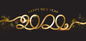 Happy New Year 2020. The inscription is made of curved gold ribbons. Golden numbers with ribbons and confetti on a dark background. Congratulation on winter holidays.