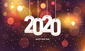 Happy new year 2020. Hanging white paper number with confetti on a colorful blurry background.