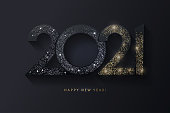 istock Happy New Year 2021 design. Modern 2021 glittering black and gold numbers isolated on black background. 1258742581