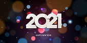 Happy New Year 2021. Holiday greeting card design. White paper numbers on a defocused colorful, bokeh background.