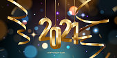 Happy New Year 2021. Hanging golden 3D numbers with ribbons and confetti on a defocused colorful, bokeh background.