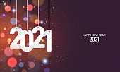 Happy new year 2021. Hanging white paper number with confetti on a colorful blurry background.
