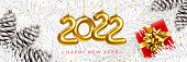 istock 2022 Happy New Year Greeting Card. Christmas composition with Pine Cones, white Spruce Branches, Christmas Decorations in the form of Numbers 2022, Gift Box 1327173459