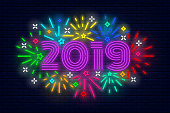 Happy New Year 2019 poster. Colorful vivid fireworks. Light, bright neon banner at brick wall. Elements for presentations, flyers, leaflets, posters or postcards. Vector, isolated, eps 10.