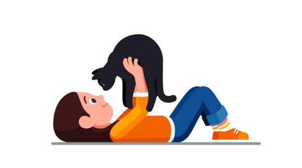 stockillustraties, clipart, cartoons en iconen met gelukkig preschool meisje liggend op de grond houden zwarte kat op zoek in haar ogen. glimlachend kind bedrijf schattig huisdier. kind cartoon karakter platte vector clipart illustratie. - teenager animal