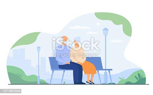 istock Happy senior couple sitting on bench in park 1271507044
