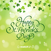 Happy St. Patrick's Day Calligraphy with the clover leaves green background