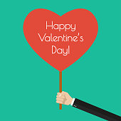 Happy Valentine's day banner in flat style. Hand holding a heart with with Valentine greeting. Vector illustration.