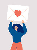 istock Happy woman holding a big envelope with a red heart above her head isolated on white background. 1195999035