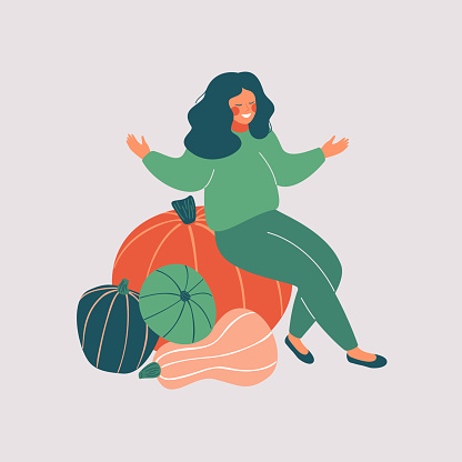 Happy woman sits on the pile of pumpkins with open arms