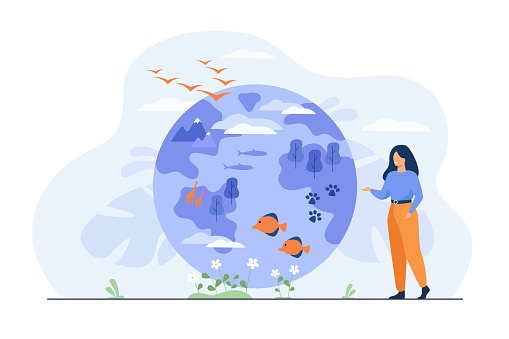 Happy woman standing and pointing on globe with flora and fauna