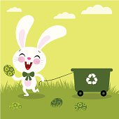 Happy Easter bunny holding an eco-friendly egg and pulling a recycling bin