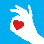 Vector illustration of  a white okay hand symbol with a red heart in it on a blue square background.