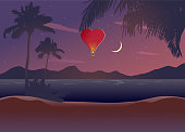 Tropical beach at night, no people, serene scene. Red heart shape air balloon in the sky.