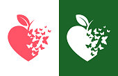 Heart shaped apple symbol with butterflies flying away - stylized cut out icon