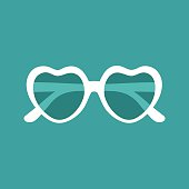 Vector illustration of heart shaped sunglasses on green background.
