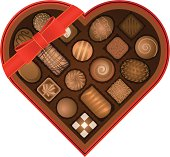 An open heart-shaped box with ribbon, full of chocolate candy.