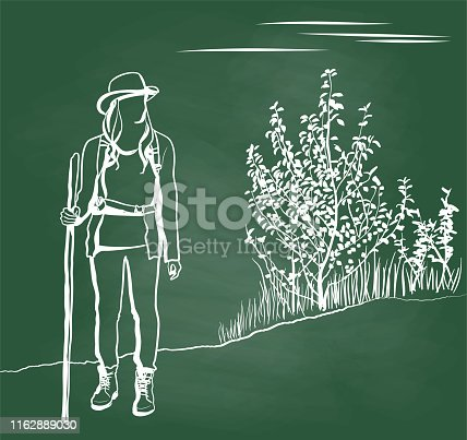 Beautiful young woman in hiking outfit standing and holding a walking stick