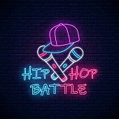 Hip hop battle neon sign with two microphones and baseball cap. Emblem of rap music. Dance contest advertisement design. Bright banner, logo. Vector illustration.