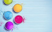 Holi background flat lay. Colorful holi powder on blue wooden background. Vector illustration