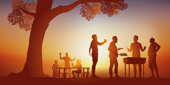 Holiday concept, with friends having a good time around a barbecue.
