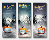 istock Holiday Halloween banners with pumpkins wearing medical face mask and silhouettes of bats, dead trees and big moon. Halloween festival in Covid-19. Coronavirus concept. Vector 1284637487