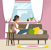 Young woman with a laptop working or entertaining on a sofa at home.